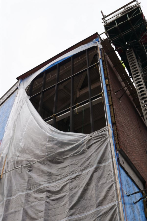 """The opening in the poly weather shield reveals the steel structure in place to support the glass """"curtain wall"""" of the Beacon, a signature feature of the Bonney building. (Doug Hubley/Bates College)"""