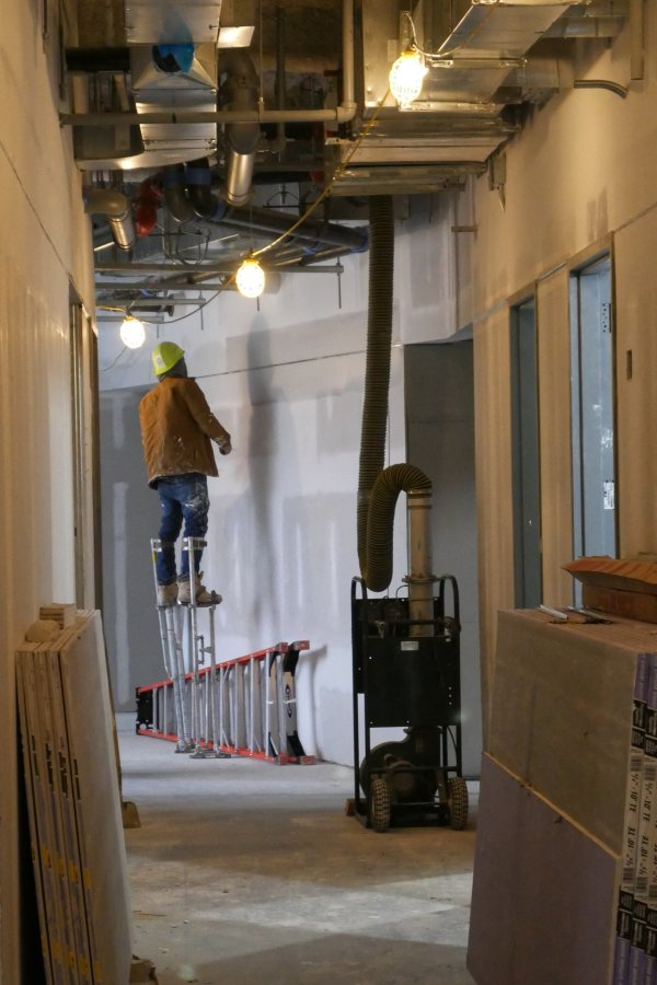 """Wearing stilts, a drywall """"mud"""" applicator is at work on the second floor of the science center. Working in pairs, one on stilts and one not, these workers can work inpressively fast. (Doug Hubley/Bates College)"""