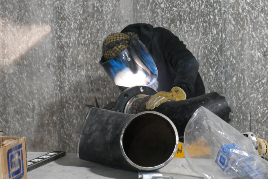 Shown in the Bonney center penthouse, a welder prepares a section of stormwater drainpipe for joining. (Doug Hubley/Bates College)