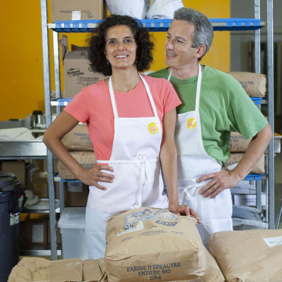 """Beth George '85 and Tim Kane '85 outside and inside of their family-owned company, Spelt Right, Inc., located in Yarmouth's Sparhawk Mill at 81Bridge Street, overlooking the Royal River. The river powers the mill.  Spelt Right® is a small family owned Maine company that specializes in baked goods made with organic spelt flour and other organic and all natural ingredients.  We started Spelt Right in 2007 as a result of our discovery that our young son was sensitive to common wheat (triticum aestivum).  In our search for alternative great tasting, healthy grains that he could enjoy, we found spelt (triticum spelta), an ancient cousin of common wheat.  Unable to find """"kid friendly"""" spelt products in the market place, we decided to make them ourselves.  In June 2008, we moved our facility to the historic and green Sparhawk Mill (the bakery is powered by water from the Royal River) in beautiful Yarmouth, Maine expanding our capacity to meet our growing sales to health and specialty food stores, supermarkets, local restaurants, educational institutions, and to people like you!    If you are in the area and would like to visit the facility, please call us for a scheduled tour."""