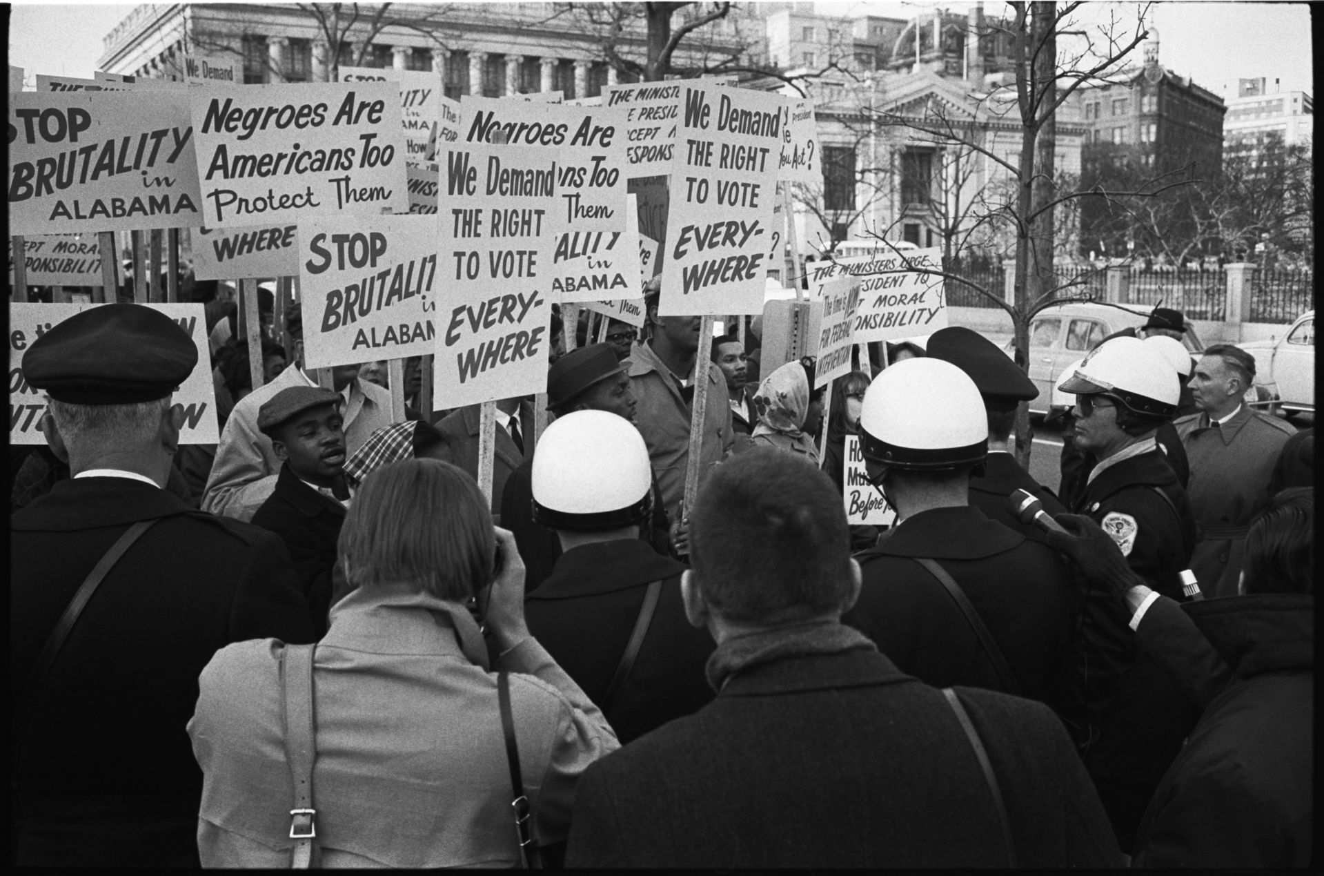 """[African American demonstrators outside the White House, with signs """"We demand the right to vote, everywhere"""" and signs protesting police brutality against civil rights demonstrators in Selma, Alabama] / WKL.  Leffler, Warren K, photographer. African American demonstrators outside the White House, with signs """"We demand the right to vote, everywhere"""" and signs protesting police brutality against civil rights demonstrators in Selma, Alabama / WKL. Alabama Selma Washington Washington D.C, 1965. Photograph. https://www.loc.gov/item/2014645538/."""