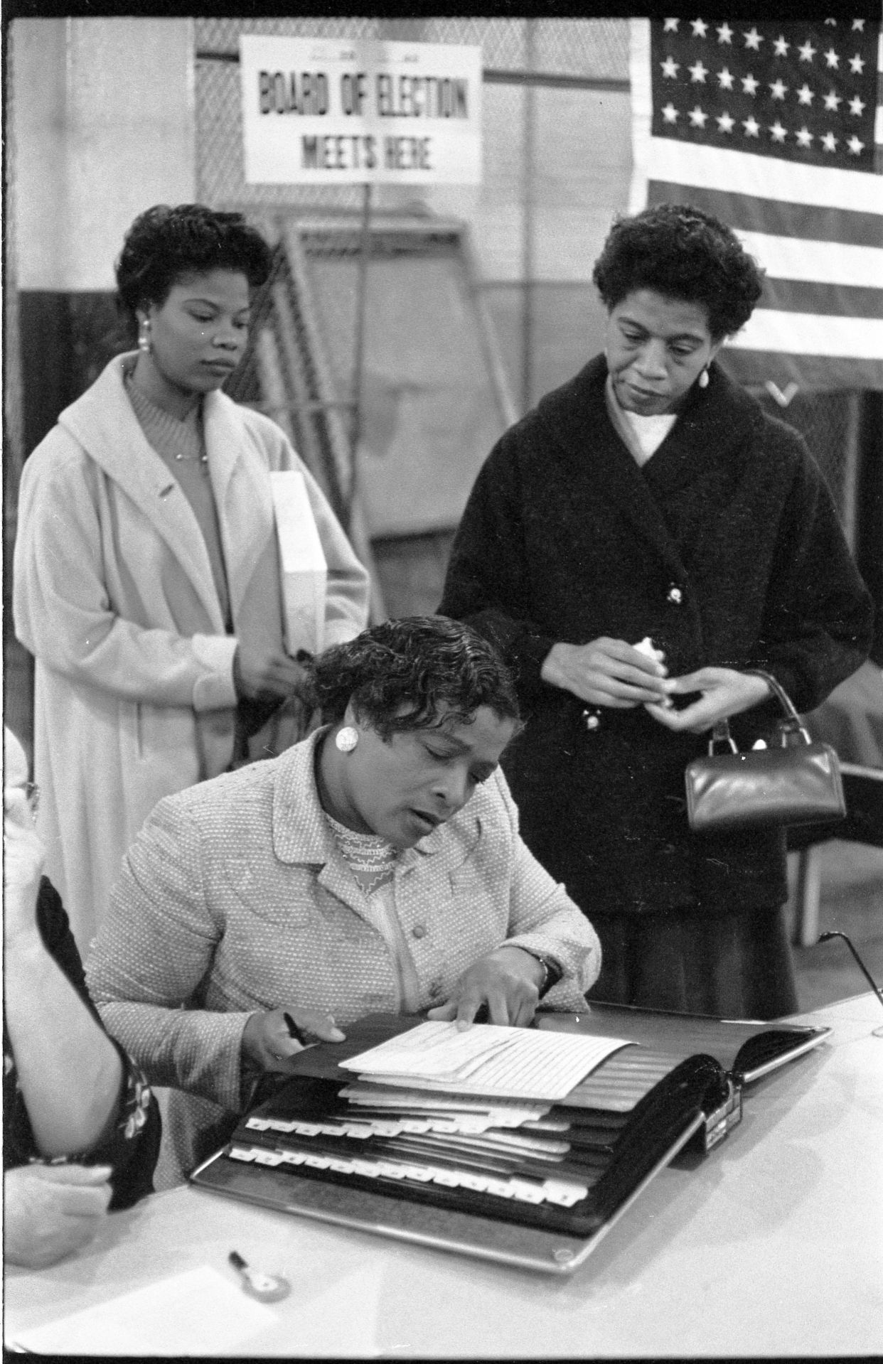 http://hdl.loc.gov/loc.pnp/ds.08063  [Three women at a polling place, one looking at a book of registered voters on November 5, 1957, in New York City or Newark, New Jersey] / TOH.  O'Halloran, Thomas J, photographer. Three \women at a polling place, one looking at a book of registered voters on November 5, in New York City or Newark, New Jersey / TOH. United States, 1957. [5 Nov] Photograph. https://www.loc.gov/item/2015651653/.