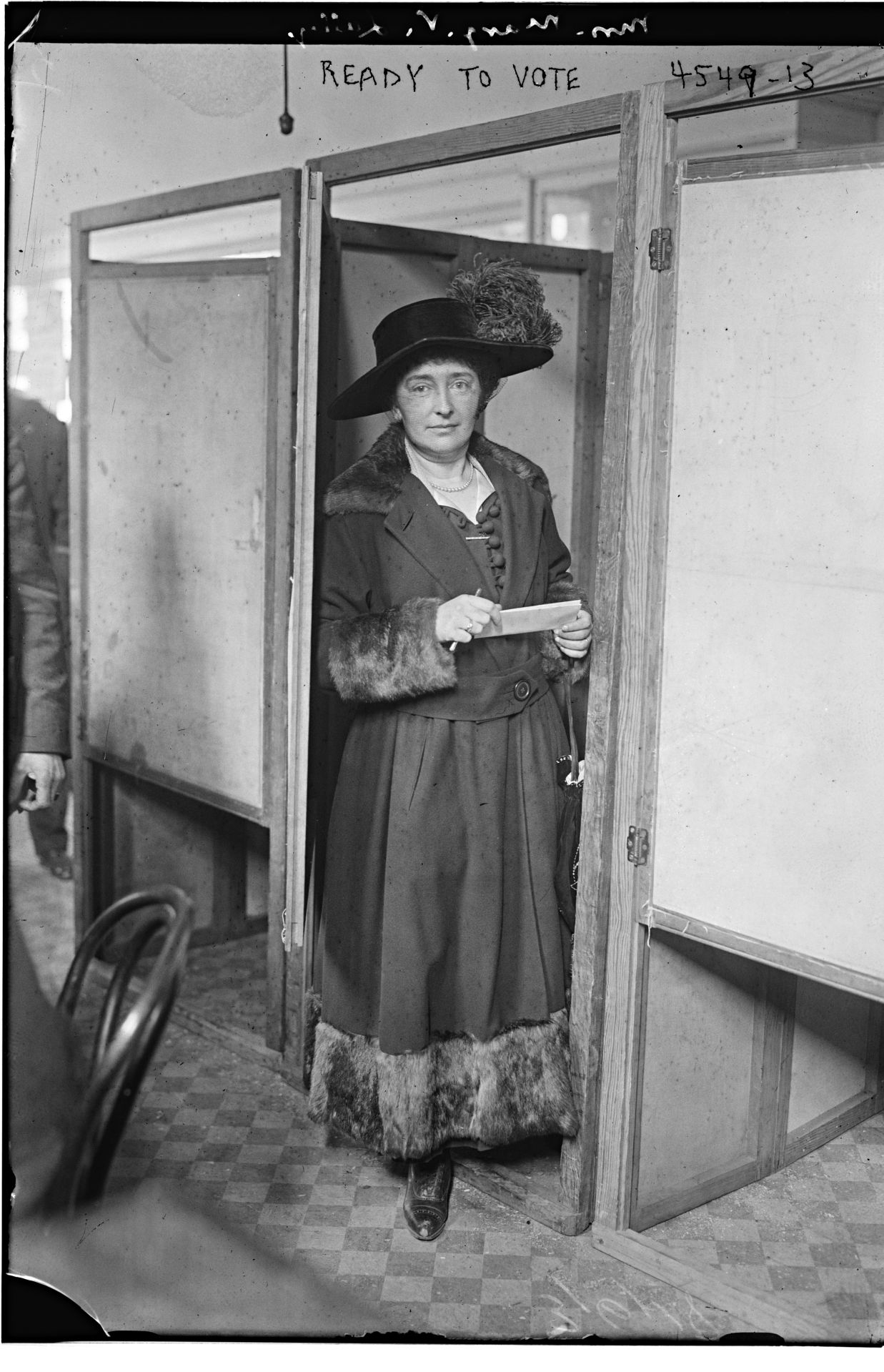 Photograph shows Margaret V. Lally at the door of a voting booth during the first election where women could vote, New York City. (Source: Flickr Commons project, 2016)  Bain News Service, Publisher. Ready to Vote. , 1918. [March 5] Photograph. https://www.loc.gov/item/2014706759/.