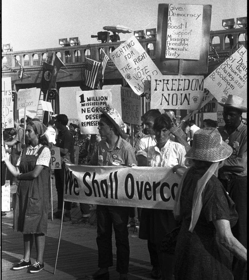 """Leffler, Warren K, photographer. Black and white supporters of the Mississippi Freedom Democratic Party holding signs in front of the convention hall at theDemocratic National Convention, Atlantic City, New Jersey; one sign reads """"Fighting for the right to vote MFDP"""" / WKL. Atlantic City New Jersey, 1964. Photograph. https://www.loc.gov/item/2014645515/."""