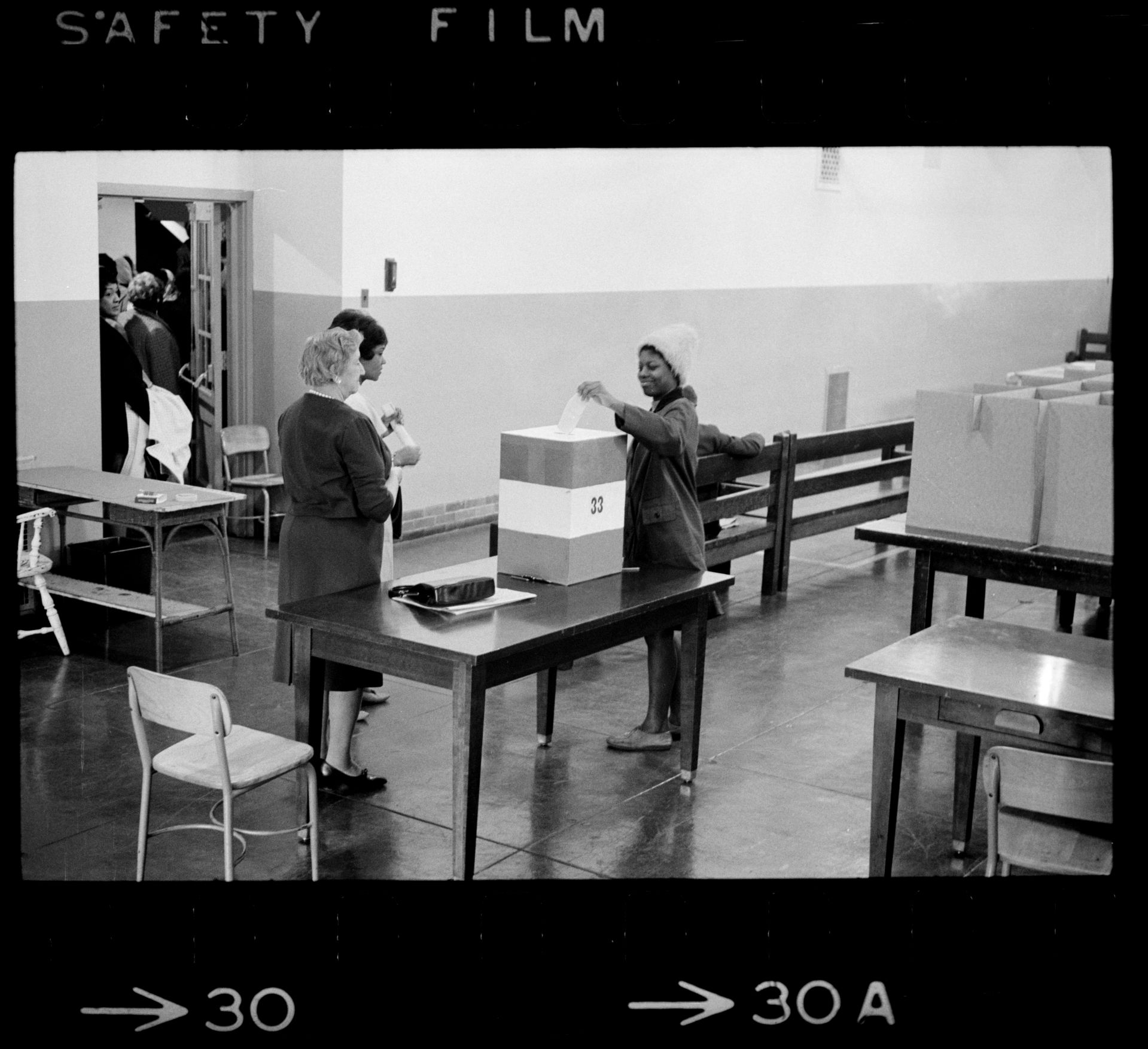 Negro voting in Cardoza [i.e., Cardozo] High School in [Washington,] D.C. / [MST].SummaryPhotograph showing a young African American woman casting her ballot.Trikosko, Marion S, photographer. Negro voting in Cardoza i.e., Cardozo High School in Washington, D.C. / MST. Washington D.C, 1964. Nov. 3. Photograph. https://www.loc.gov/item/2003688167/.