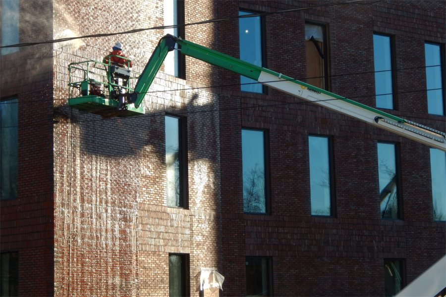 Washing brickwork on the science center's south wall. (Doug Hubley/Bates College)