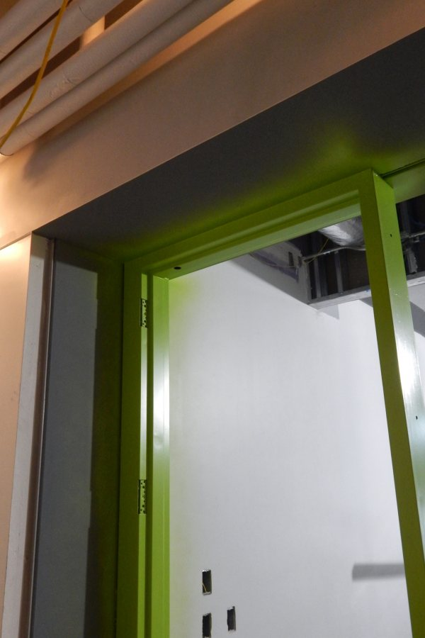 "The green and gray around this first-floor doorway are finish coats of paint. The ""peach"" is actually white primer, color-shifted by the camera. (Doug Hubley/Bates College)"