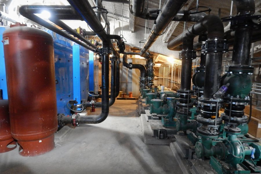 Located in the Bonney center penthouse, the blue boilers at left will heat water for both domestic use (handwashing, etc.) and space heating. At right is a battery of water pumps. (Doug Hubley/Bates College)
