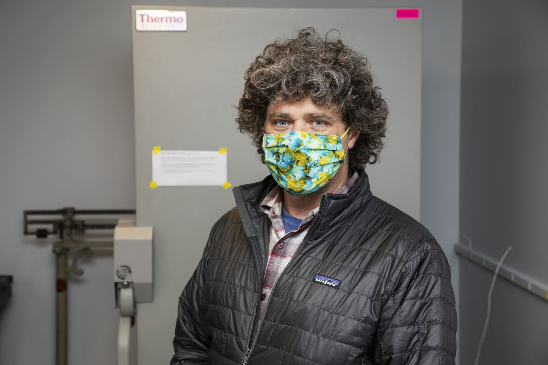 Brett A. Huggett, associate professor biology, poses next to a Thermo Scientific freezer seen inside Carnegie Science Hall at Bates College on December 15, 2020.