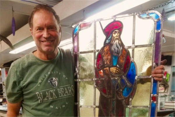 Jim Nutting '76 poses with the newly restored Gomes Chapel stained glass panel depicting Leonardo da Vinci. (Courtesy of Jim Nutting '76)