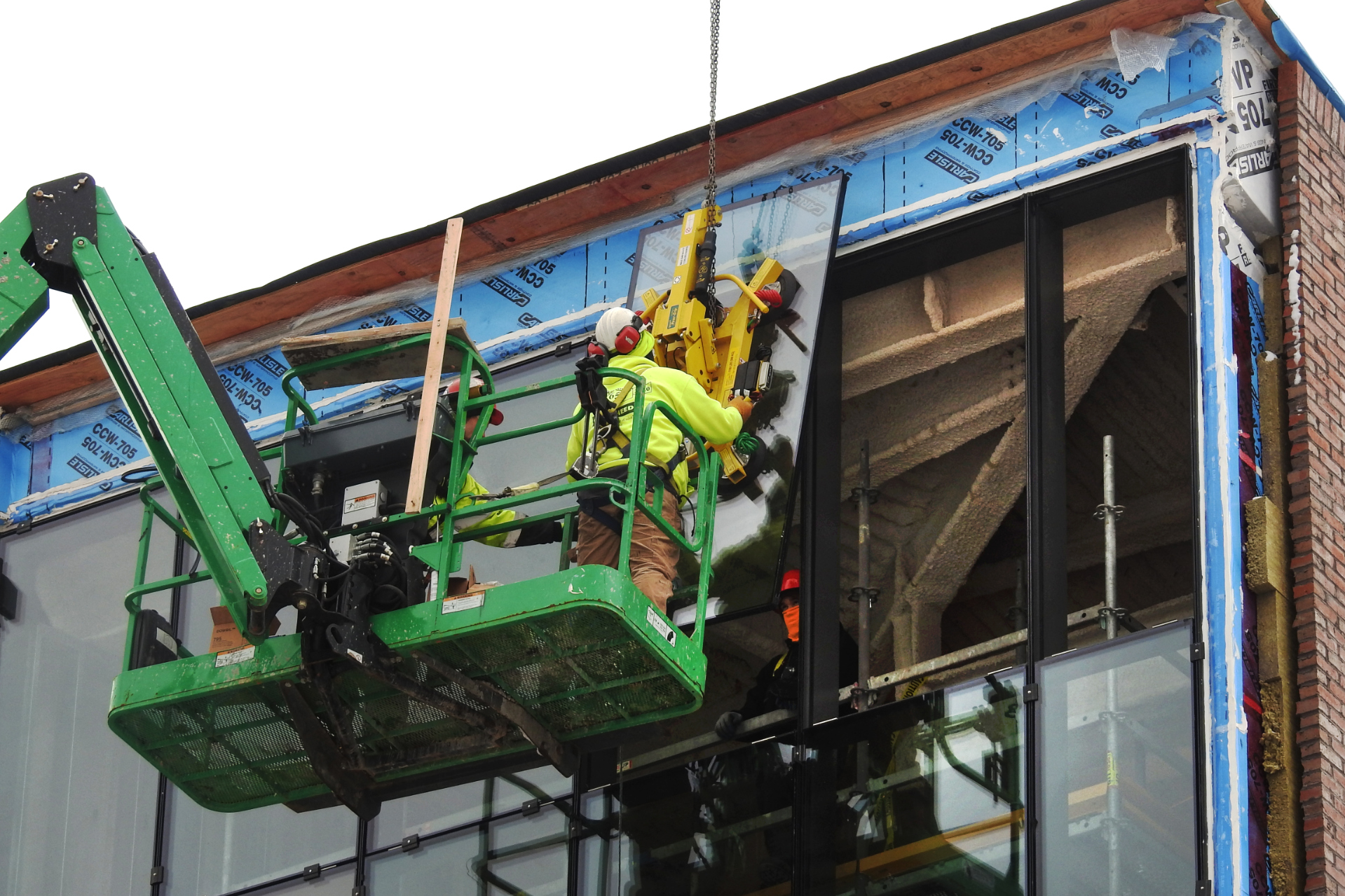 The final panes of glass are installed on the Beacon at the Bonney Science Center by workers from Lockheed Window and O&P Glass. The yellow contraption is a vacuum lifter that holds and maneuvers the pane. (Jay Burns/Bates College)