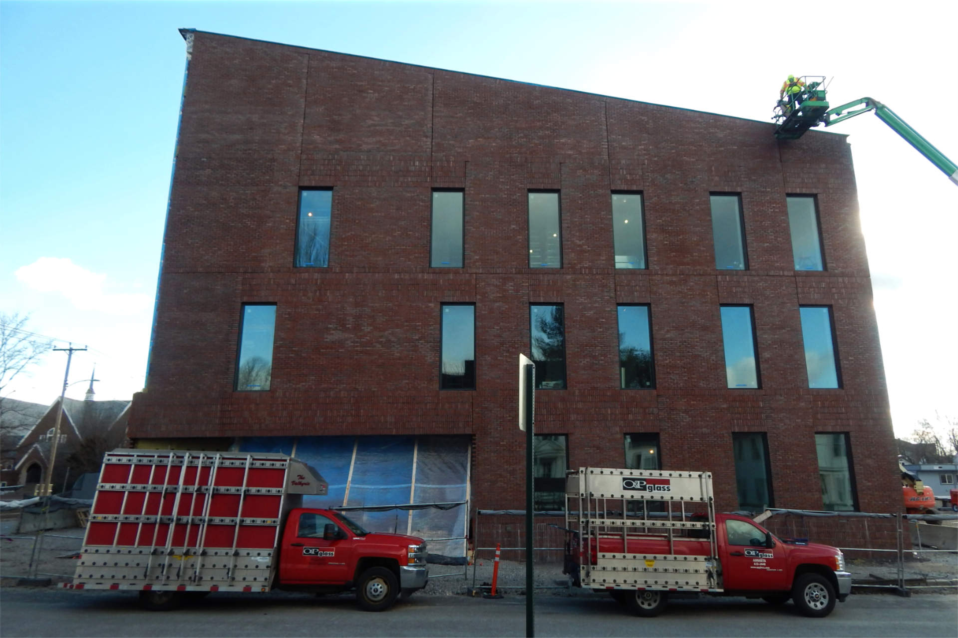 Trucks from the Augusta, Maine, architectural-glass firm of O&P sit on Nichols Street near the Bonney Science Center early on Dec. 29. With Lockheed Window Corp. of Rhode Island providing additional hands, O&P is the glass subcontractor for the science center project. (Doug Hubley/Bates College)