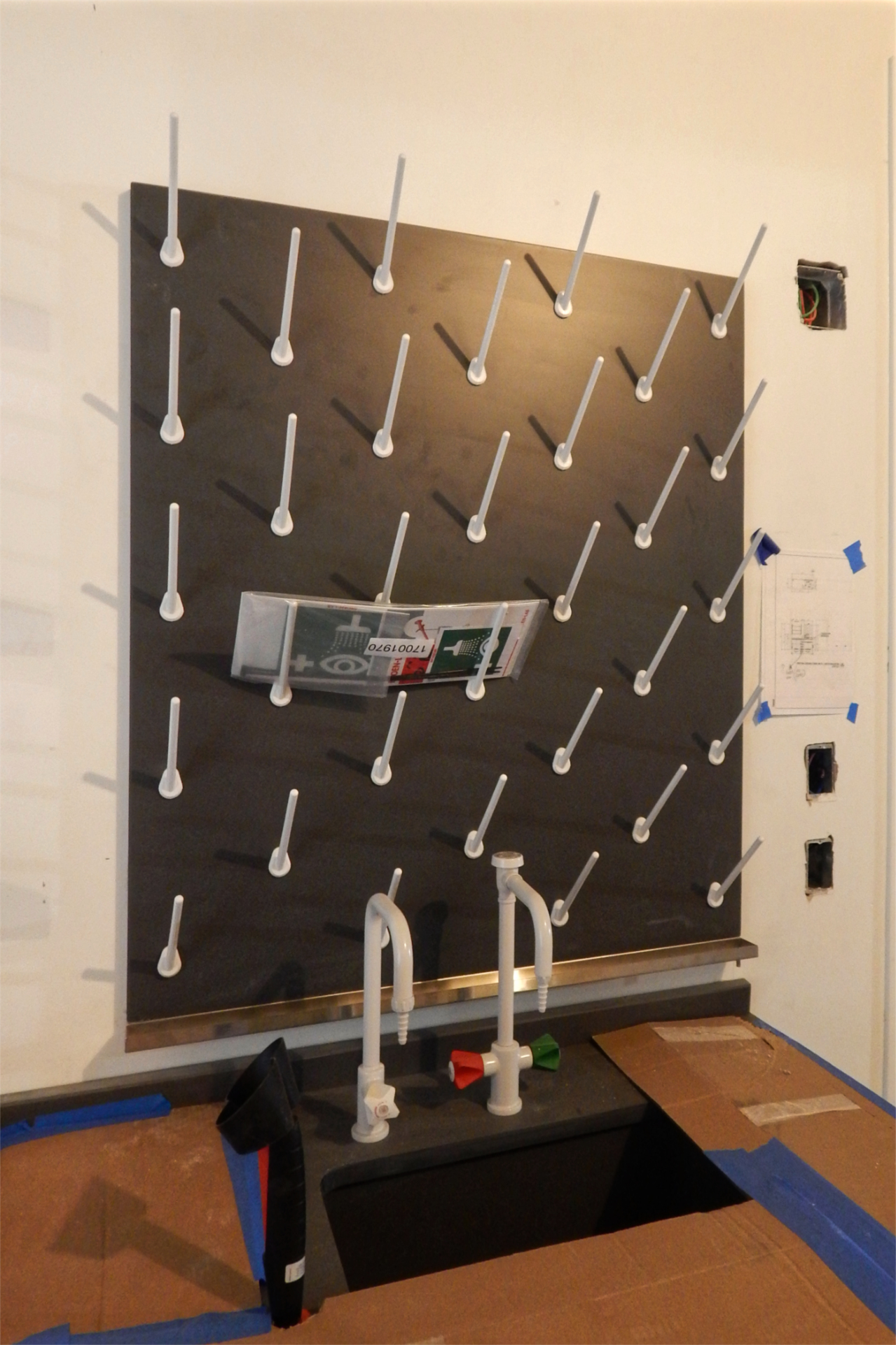This pegboard will be used to dry lab vessels after washing. Note the gutter at the bottom of the board and its little drain at the right-hand end. (Doug Hubley/Bates College)