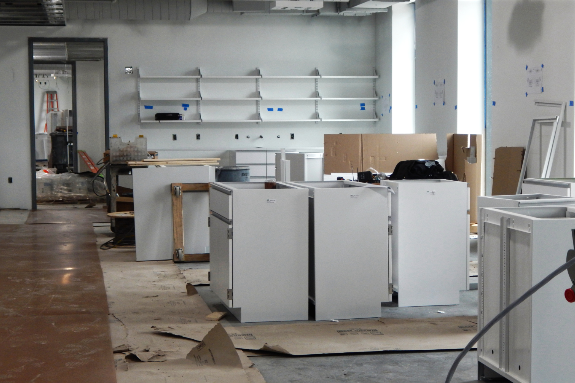 Cabinets await placement in a second-floor research lab that will be shared by faculty in biology and biochemistry. White is the permanent wall paint color here, but more coats will follow the initial top coat that's shown. (Doug Hubley/Bates College)