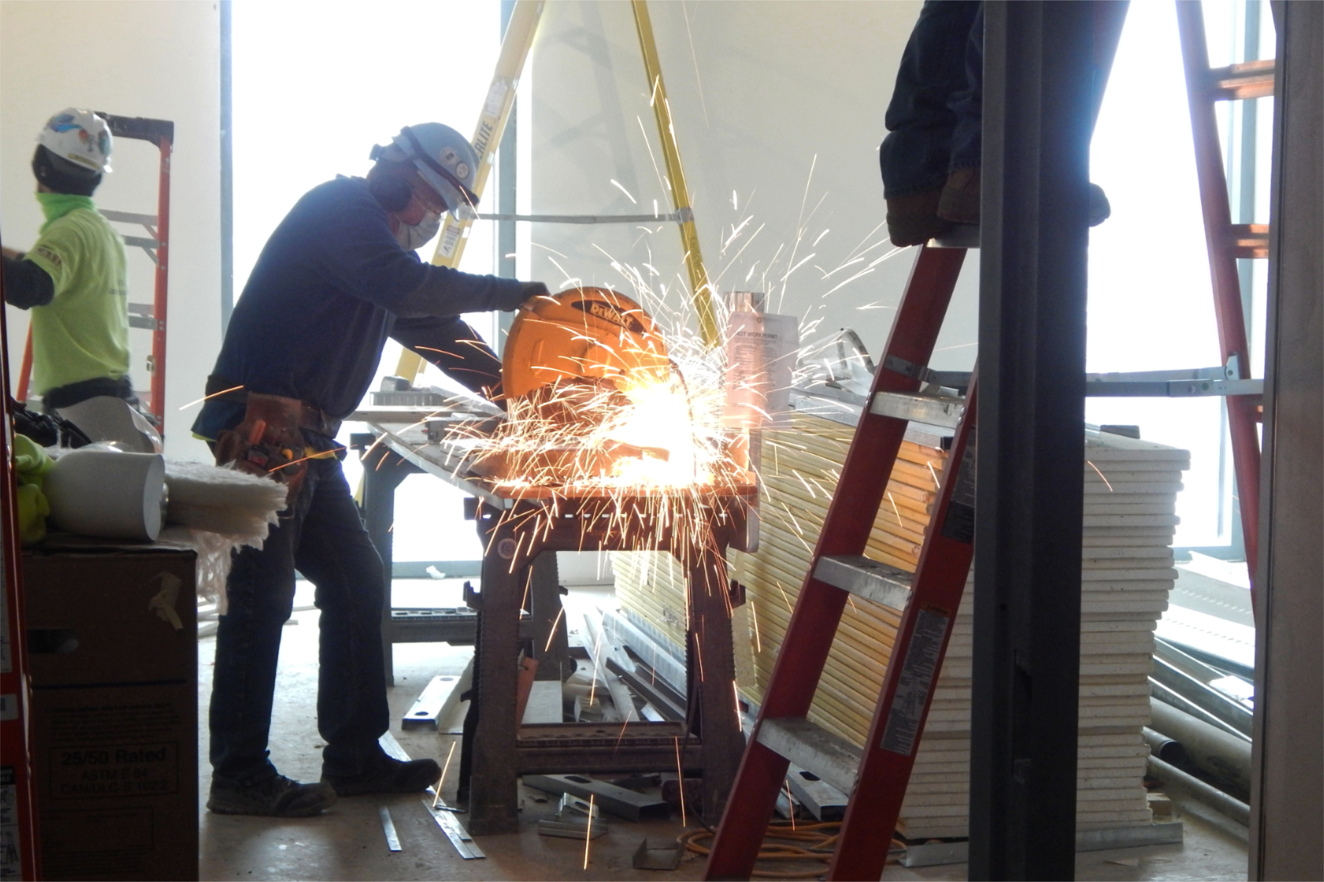 A Roland's Drywall employee cuts a section of metal wall framing. (Doug Hubley/Bates College)