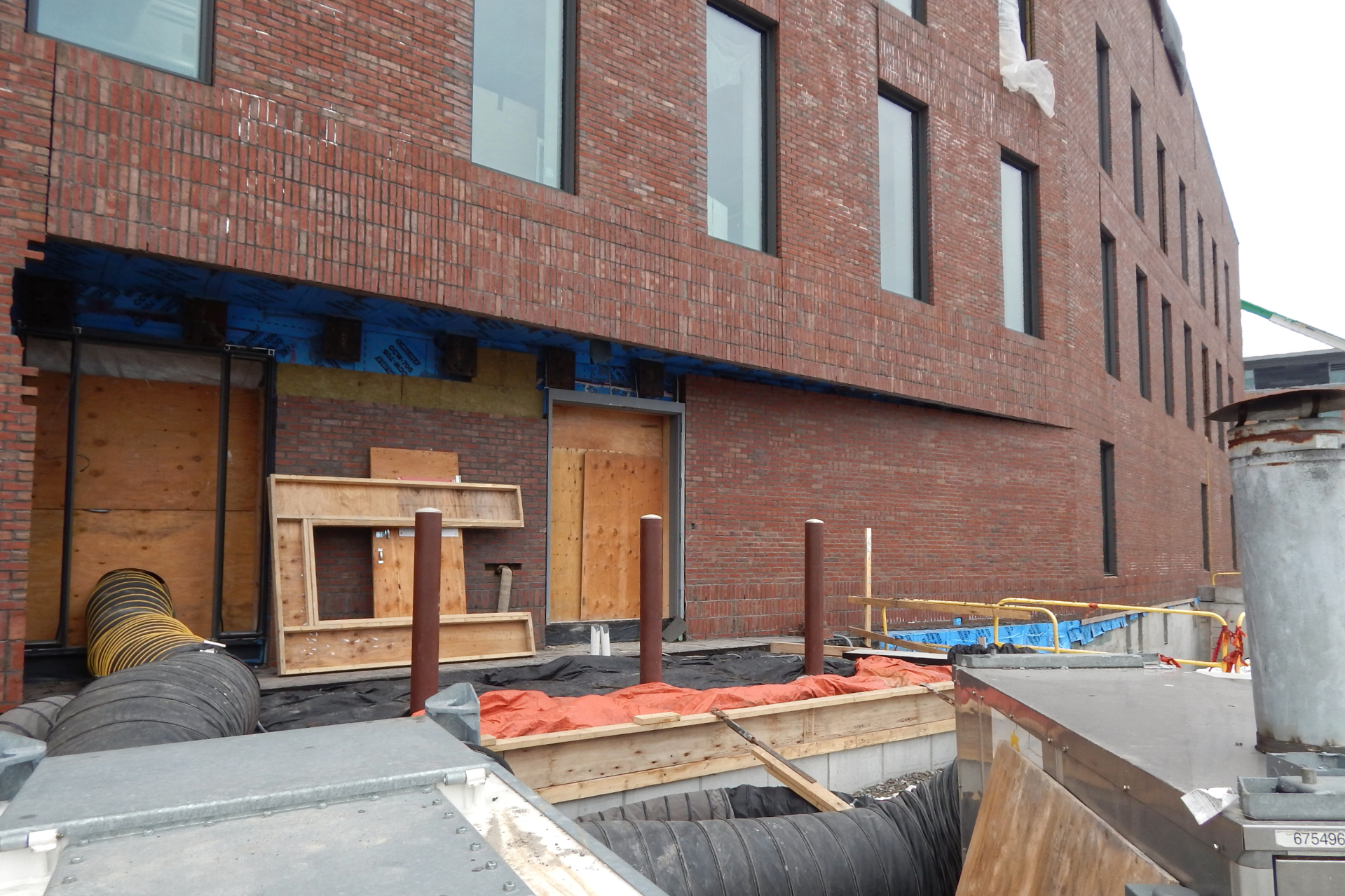 A loading dock under construction on the science center's south side. The black and orange fabrics are blankets to keep concrete warm as it cures. The accordion tube brings heat into the building from the temporary space heater in the foreground. (Doug Hubley/Bates College)