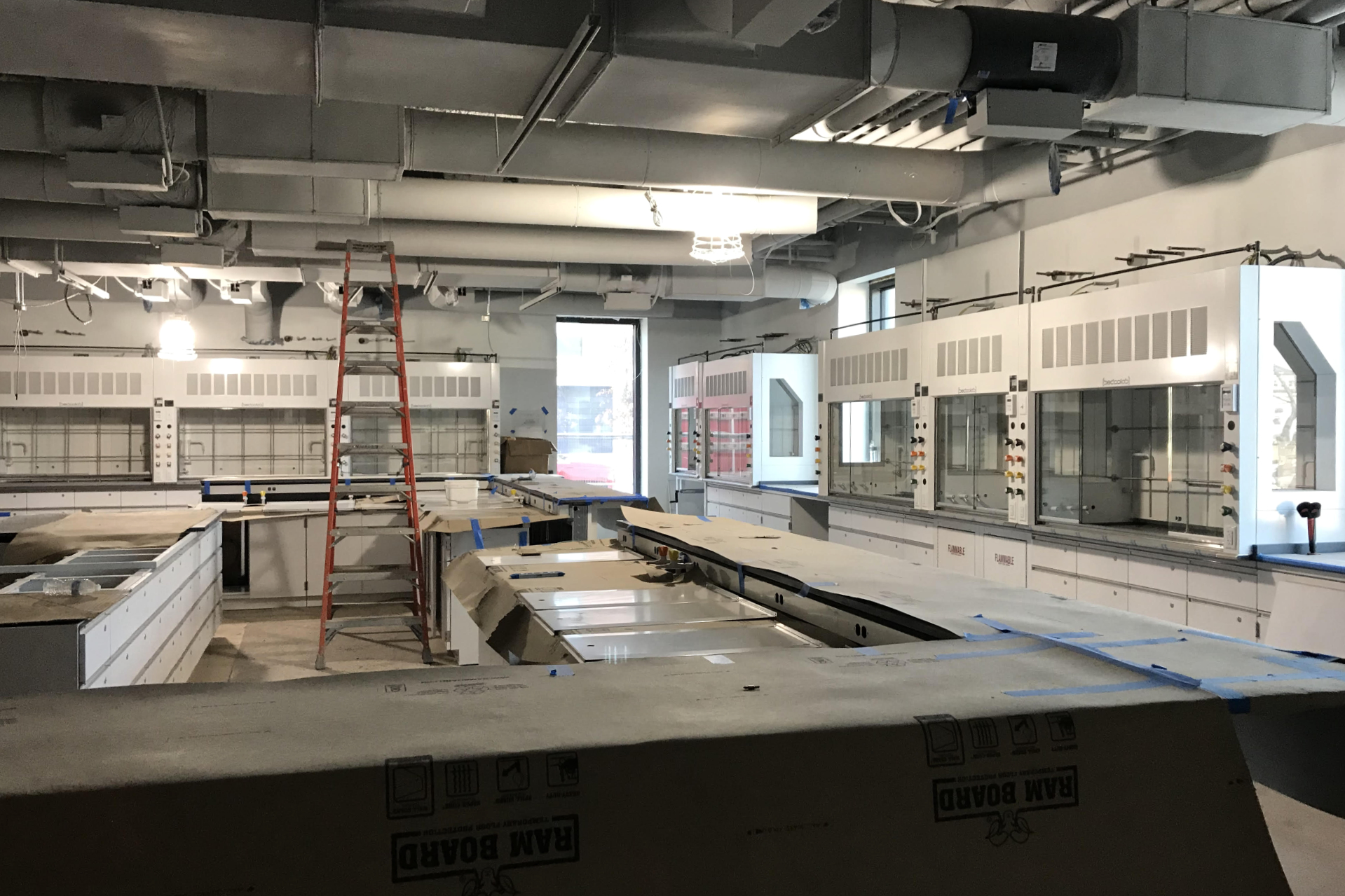 Glass-fronted fume hoods are among the science equipment newly installed in this first-floor biology lab. Students will work at the counter at center, with their professor using the smaller counter at left. (Courtesy of Consigl Construction)