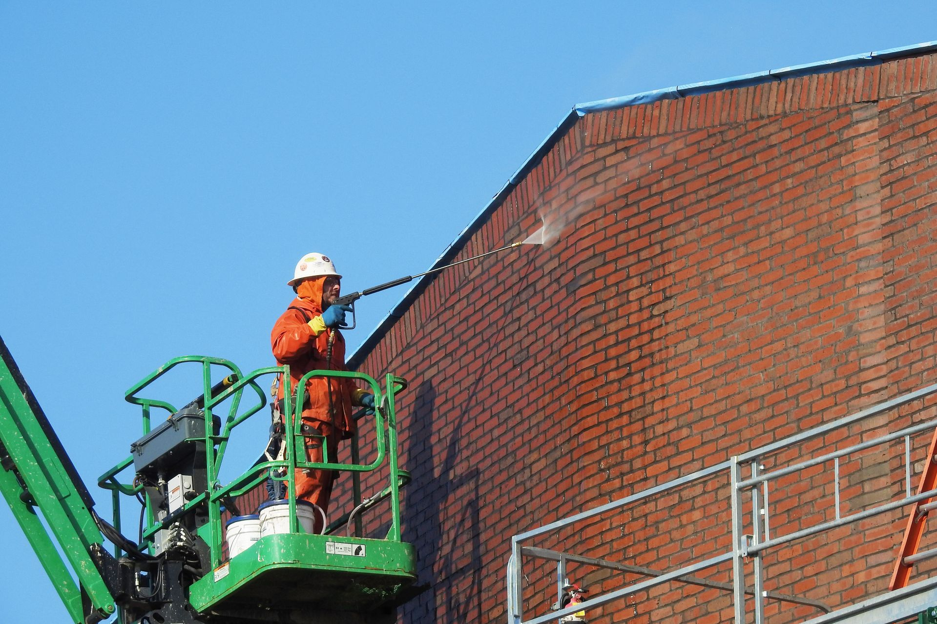 Images of interior spaces (lounges, classrooms, labs, stairwells) and exteriors of the Bonney Science Center.A worker power washes brick exterior.