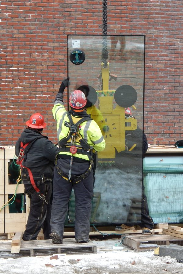 On Feb. 1, a crew from O&P Glass has uncrated a piece of glass for the Monumental Stair curtain wall and fastened the yellow vacuum lifter to it. Next, a glassworker will guide the pane as a lift carries it around the corner to its destination.  (Doug Hubley/Bates College)