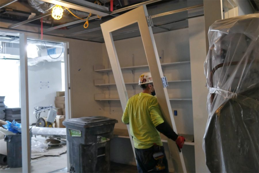 Wrangling a new door on the Bonney center's second floor. (Doug Hubley/Bates College)