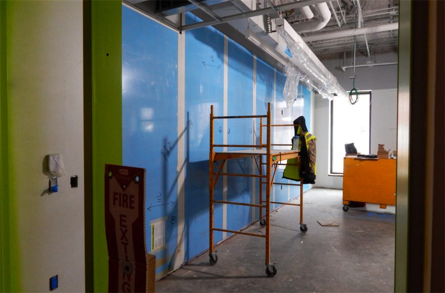 A view into a first-floor Bonney Center classroom. The blue membrane protects dry-erase whiteboards. This room will serve as a shared office for subcontractors as the Bonney project enters its final months. (Doug Hubley/Bates College)