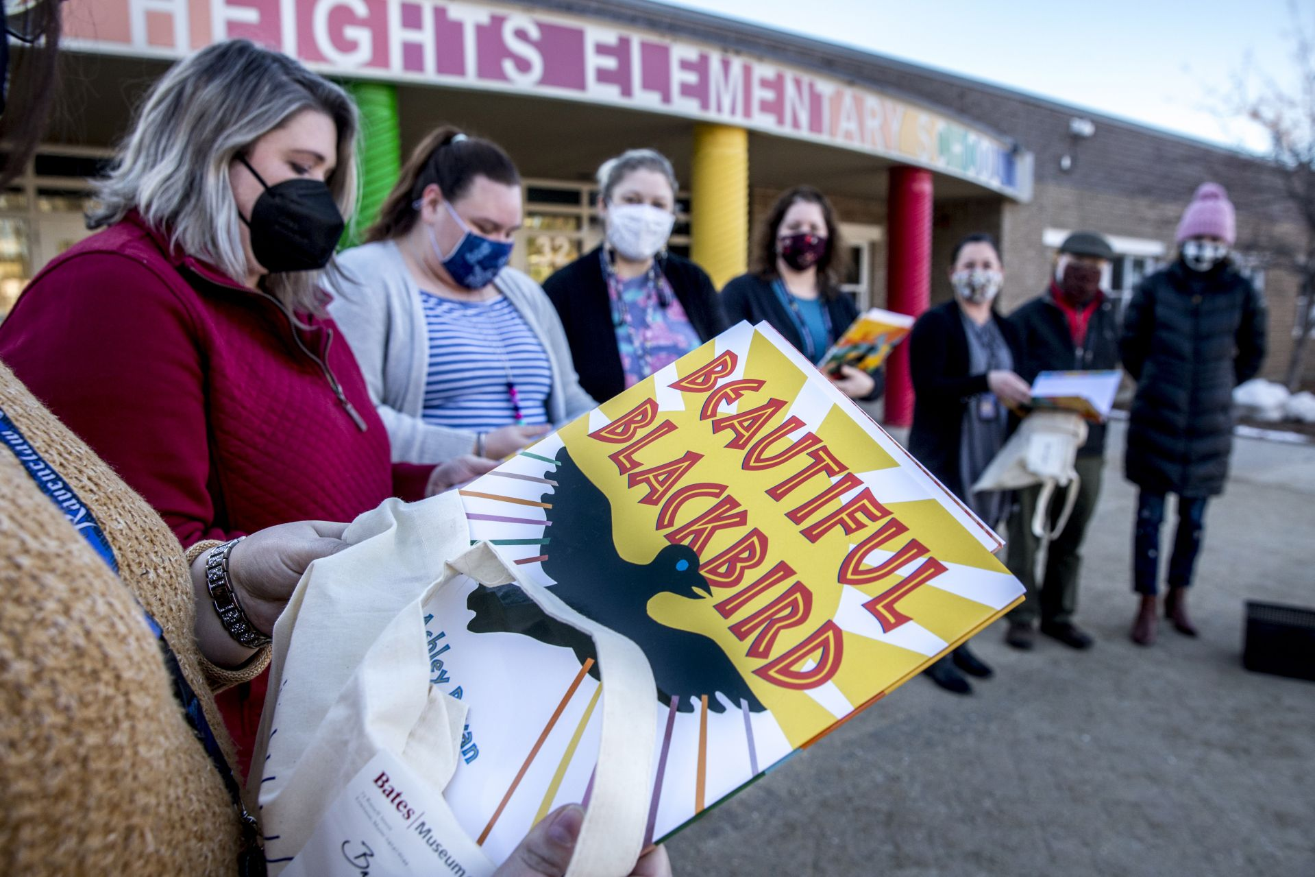 """Sherwood Heights Elementary School teachers line up in front of the Auburn school as they receive their Ashley Bryan """"swag bags"""" delivered by the Bates College Museum of Art.   The museum has Beautiful Blackbird Festival bags to distribute to local pre-K-2 teachers, in connection to the museum's exhibition""""Let's Celebrate Ashley Bryan!"""" and in cooperation with Indigo Arts Alliance.  Each bag contains a copy of Bryan's book """"Beautiful Blackbird,"""" grade appropriate activities developed by Indigo Arts, and information about the museum's collections and programs.  From left to right: Breann Crocker, Jessica Sweetser, Skylar Cambidge, Kayla Grier, Jennifer Libby, Renee Langis, and from the Museum, Assistant Education Curator for Academic & Community Programs Caitlin Patton, and Education Curator Anthony Shostak."""