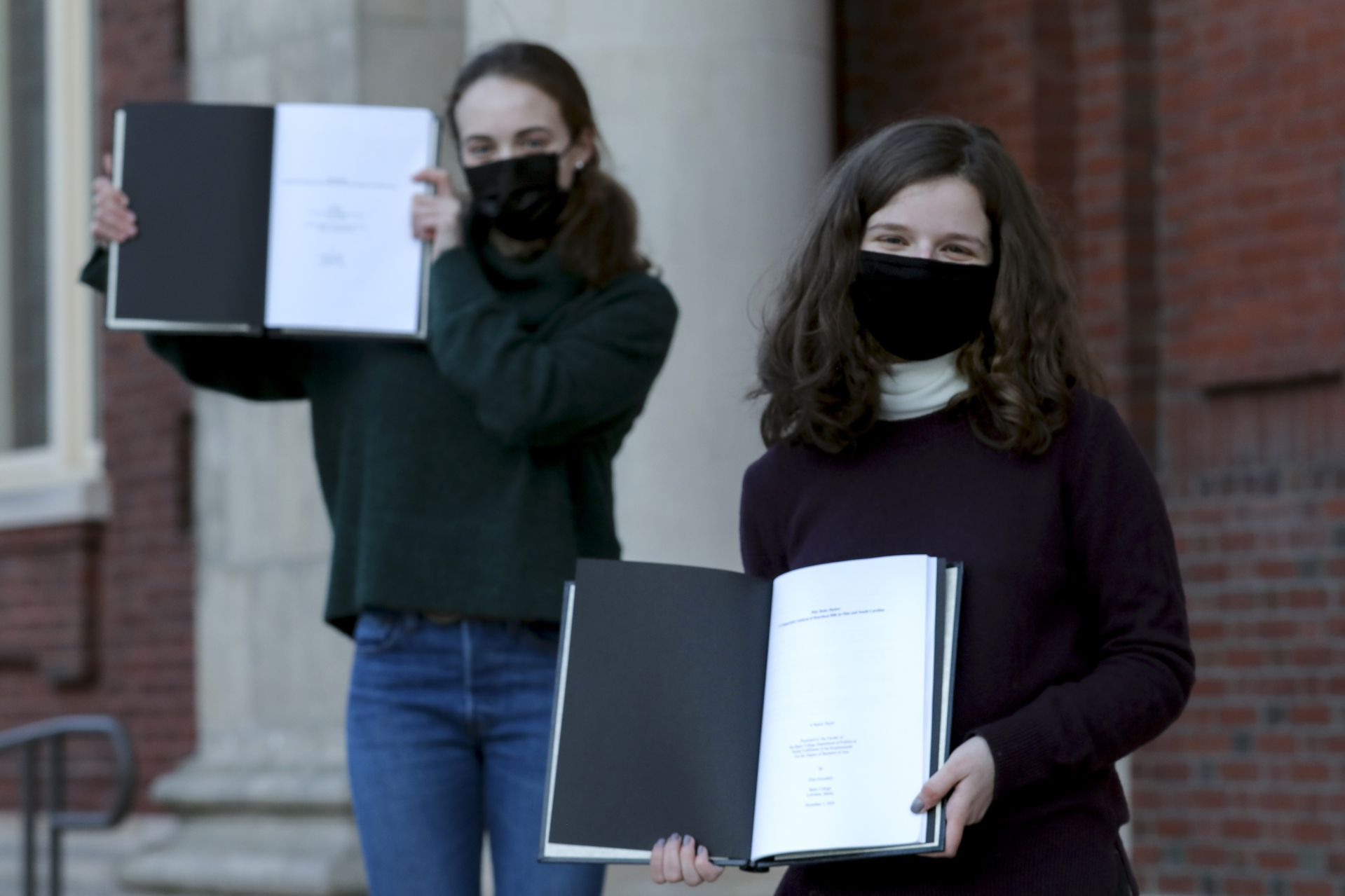 """A beloved ritual continues.(From left) Elizabeth Fairman '21 of Lathrup Village, Mich., joined Elise Grossfeld '21 of Bethesda, Md., as they bound their senior theses on the steps of Coram Library at the end of the day on March 3, 2021.""""We both finished writing our theses in December at the end of first semester but wanted to wait to bind until now. We both bound seniors' theses our freshmen year and wanted to continue on with this Bates tradition. In a year that is so different, it's so nice to be able to keep some of the most meaningful traditions.""""Grossfeld's thesis topic: """"Why Rules Matter: A Comparative Analysis of Heartbeat Bills in Ohio and South Carolina."""" Her thesis provides an analysis of how the filibuster has impacted whether or not various states have passed extreme abortion restrictions. Her thesis adviser: Professor of Politics Stephen EngelFairman's thesis topic: """"Two Detroits: Examining White Flight and Gentrification Through Critical Race Theory."""" Her thesis uses Critical Race Theory as a lens to analyze predatory housing contracts and practices against BIPOC Detroiters in the 20th century which has led to current gentrification in the city. Her thesis advisor: Visiting Assistant Professor of History Jeanne Essame"""