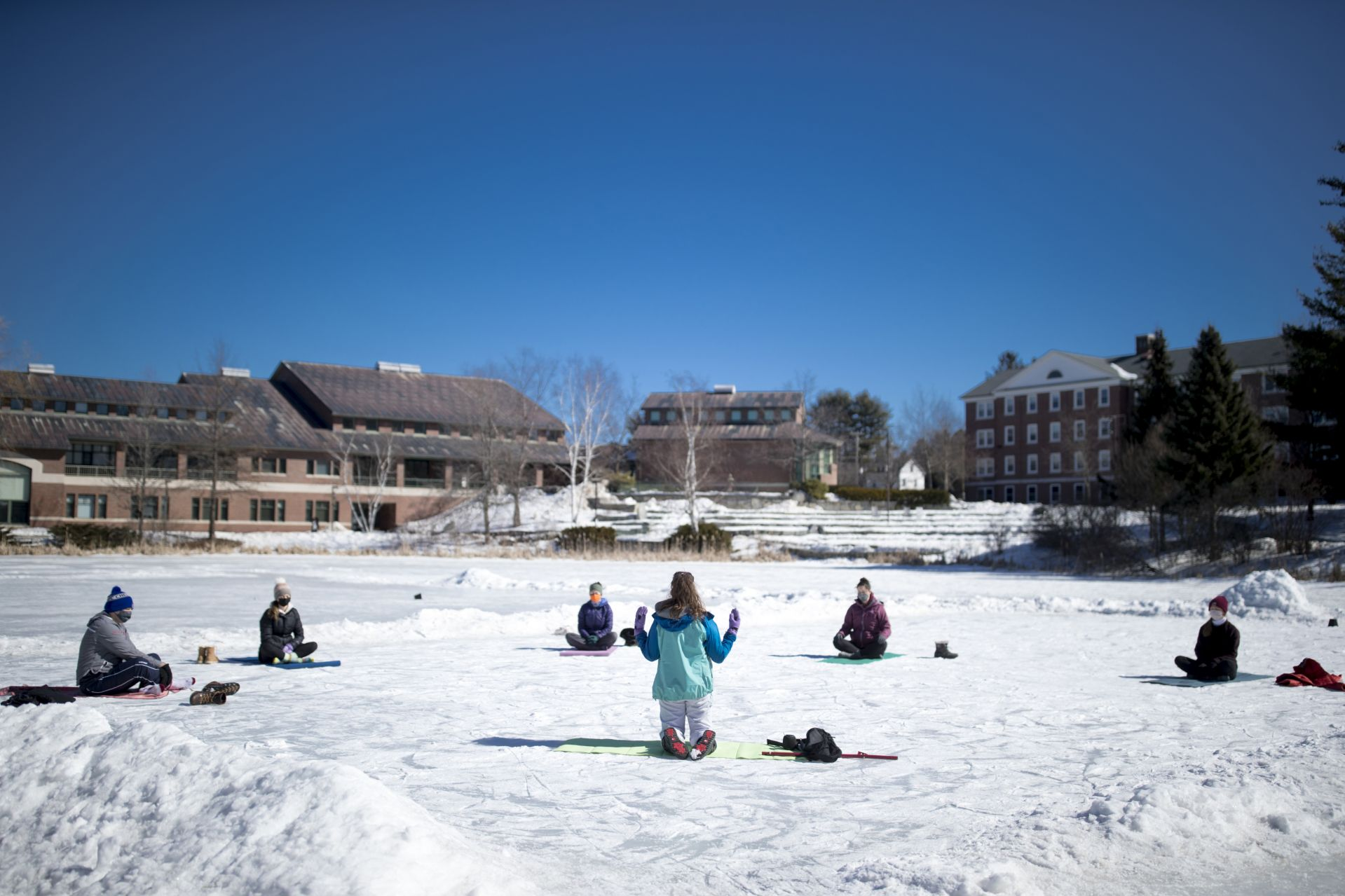 """""""I think I'm always looking for new perspectives.""""  Katia Ryan '23 of Amsterdam, N.Y., leading a group of her fellow Bobcats on a Sunday morning session of Yoga Kula on Lake Andrews.  """"You can have the same practice be it on land, ice, water and have a completely different experience,"""" Ryan says. """"At Bates we are looking for new ways to connect to the campus we love, and sometimes all you need to do to re-connect is find a fresh perspective: a new way of looking at the experience.""""  Brooks Clement (in gray sweatshirt, dark hat), Kerry Manuel, Emma Proietti, Amelia Keleher, Anna Mangum."""