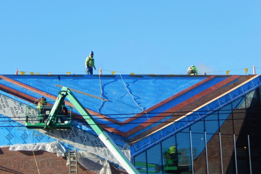 Roofers for Hahnel Brothers are working on the north roof of the Bonney Science Center on March 22, 2021. A second manlift beyond the right edge of the image is reflected in the glass curtain wall. (Doug Hubley/Bates College)