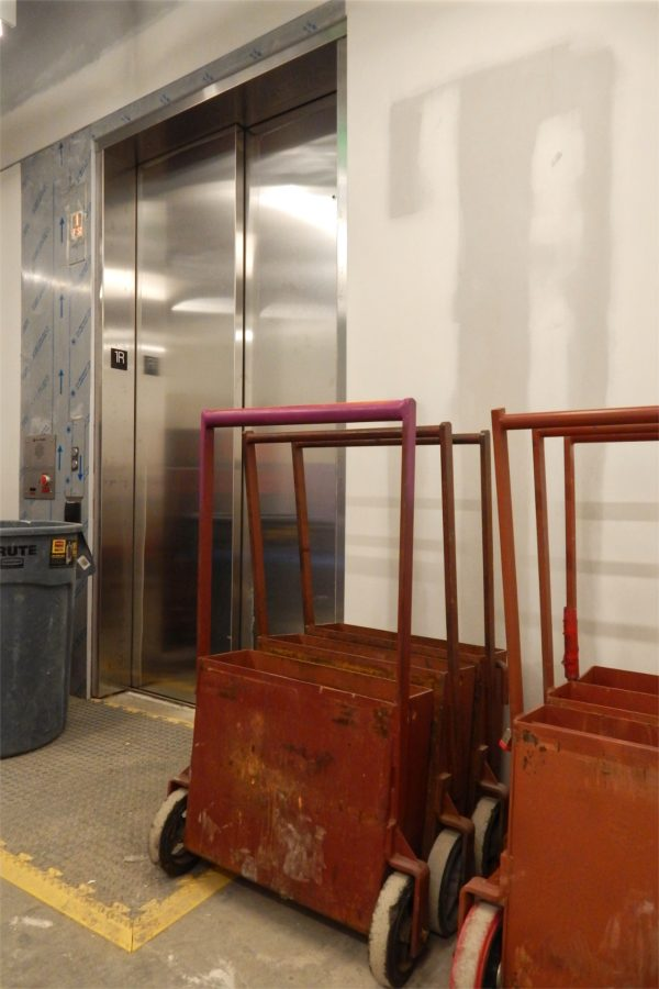 The third-floor door to the Bonney Center elevator. The red carts carry metal weights and will be used to test the elevator under load. (Doug Hubley/Bates College)