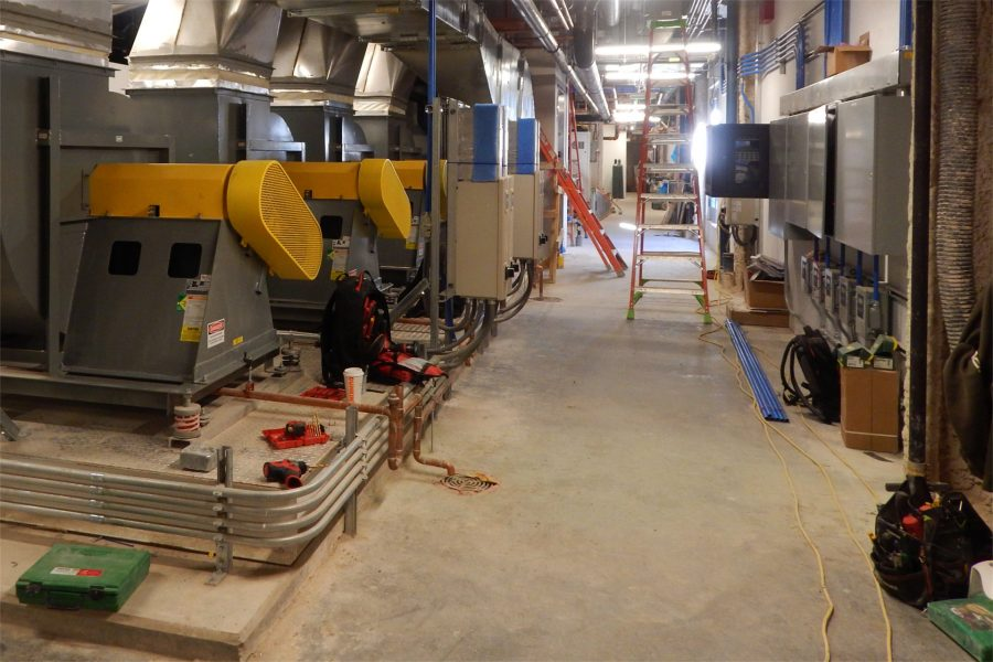 As the installation of mechanical equipment nears completion, the Bonney Center penthouse is much neater than it was a few weeks ago. The yellow and gray machines at left are air-exhaust fans. (Doug Hubley/Bates College)