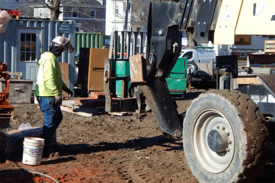A mason's tender watches as a forklift gets underway with a load of bricks bound for the Nichols Street side of the Bonney Science Center. Note the red patches on the ground at lower left where dust from cutting bricks has fallen. (Doug Hubley/Bates College)