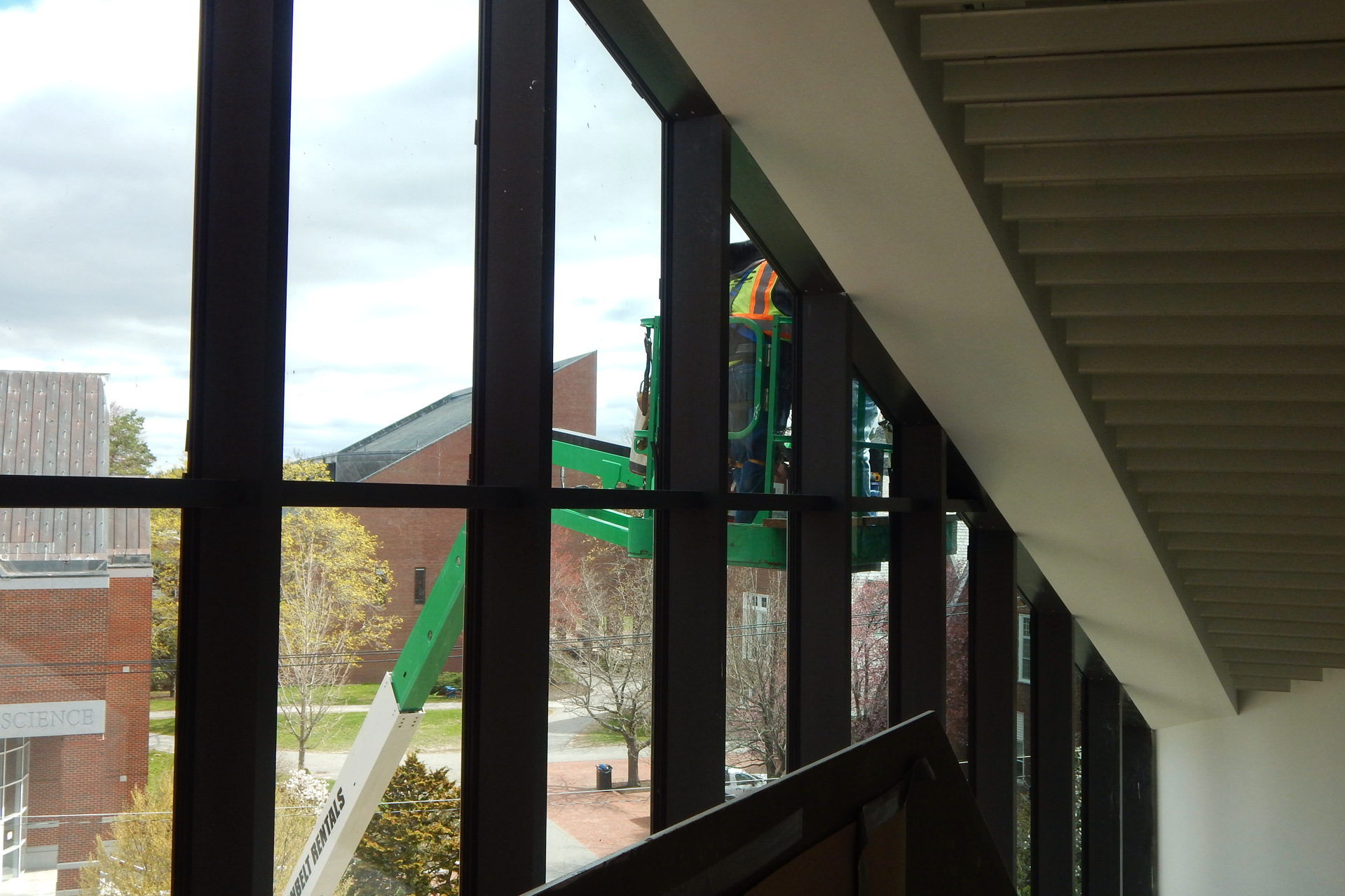 Carnegie Science Hall and Ladd Library (and roofers on a lift) seen from the head of the Bonney Center's Monumental Stair. (Doug Hubley/Bates College)