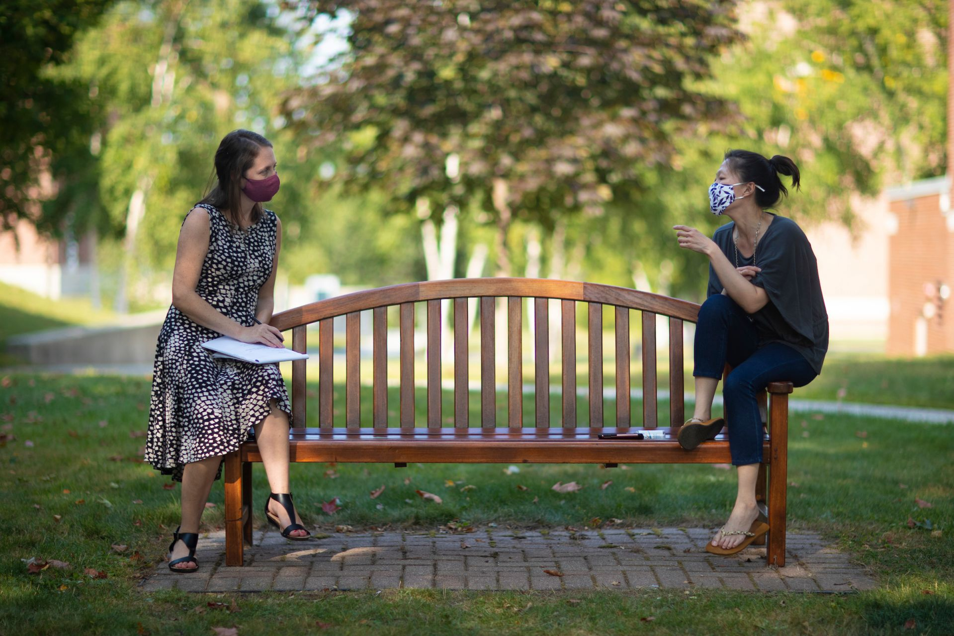 """Campus scenes on Sept. 8, 2020.  Beverly Vari and Hoi Ning Ngai, colleagues at the Bates Center for Purposeful Work, hold their weekly check-in meeting on the Historic Quad.  Besides talking strategy and tactics — from how to expand employment opportunities for students to following up on summer internships — they also """"catch up on how we're engaging in self-care — especially given the challenges of operating in a pandemic,"""" says Ngai. Prioritizing health and well-being is not just personal: """"It's a way to model that mindset for students as they become professionals."""""""