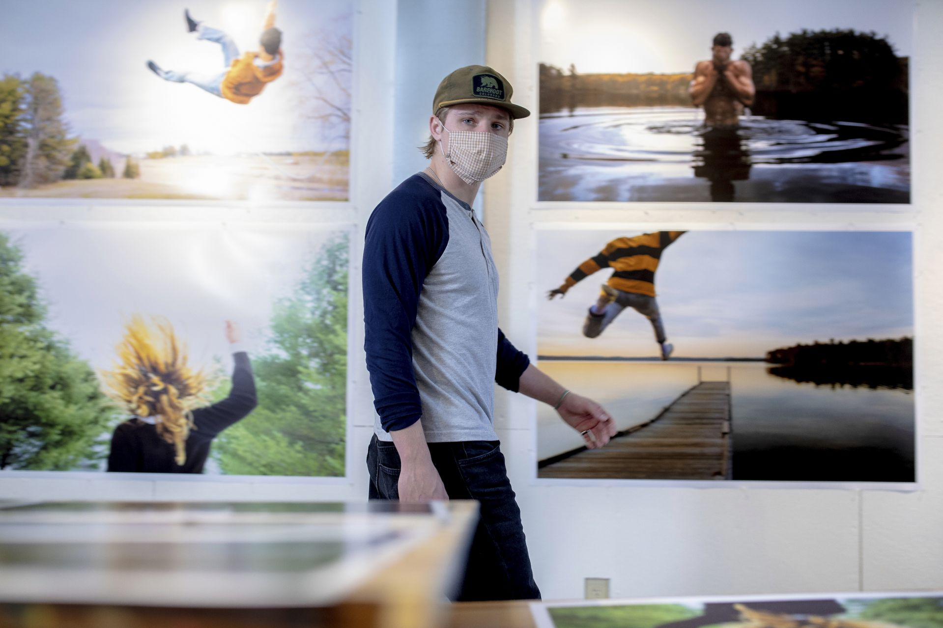 Blaise Marceau '21 of Waban, Mass., in his Olin Arts studio, paces in front of some of his work prints for his senior exhibition.