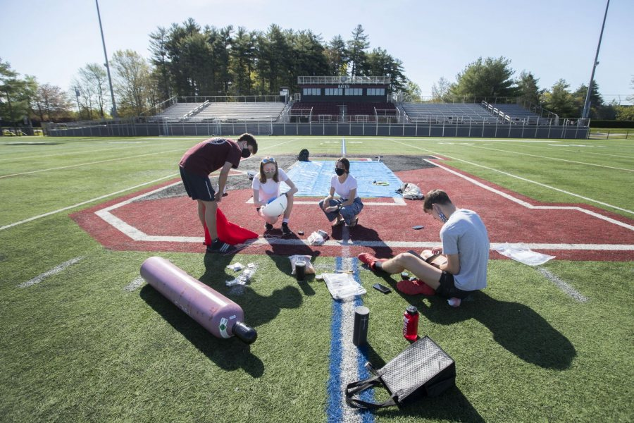 Members of the High Altitude Ballooning Club lay out their gear on May 15 in preparation for a launch from Garcelon Field. (Phyllis Graber Jensen/Bates College)