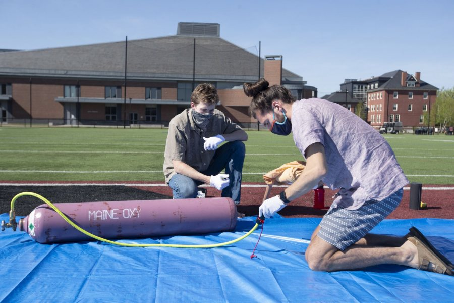 Barker and Jackson Donahue '22 of Princeton, N.J., prepare the connection to deliver helium gas to the balloon. (Phyllis Graber Jensen/Bates College)