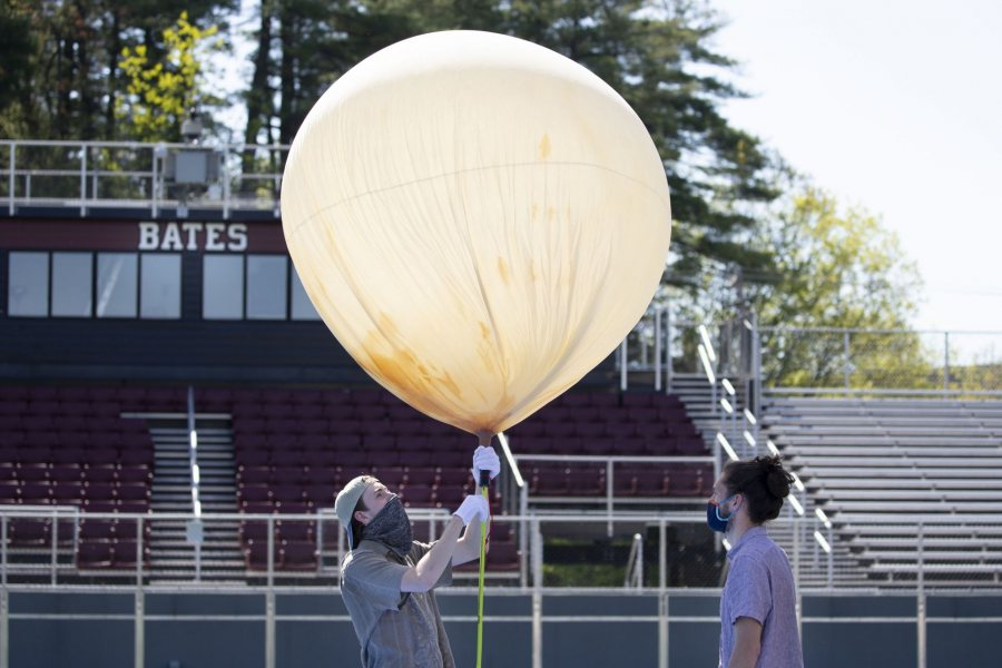 Donahue and Barker evaluate the balloon's buoyancy after filling it with helium. (Phyllis Graber Jensen/Bates College)
