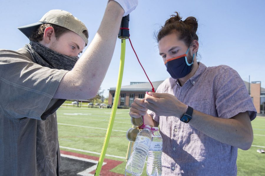 """Donahue and Barker attach a counterweight to the balloon in preparation for removing the gas hose. """"The counterweight makes the balloon easier to hold as it builds lift and helps with measuring the positive lift reading as we aim for our target lift value to stay close to the predicted launch path,"""" explains Barker."""