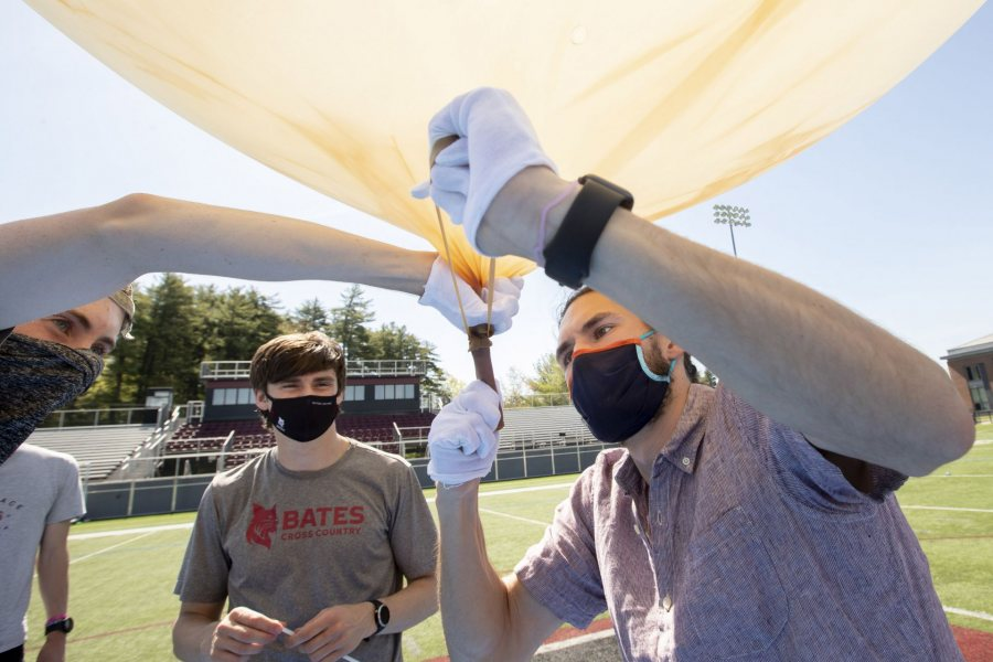 The gas hose removed, Barker ties off the balloon. (Phyllis Graber Jensen/Bates College)