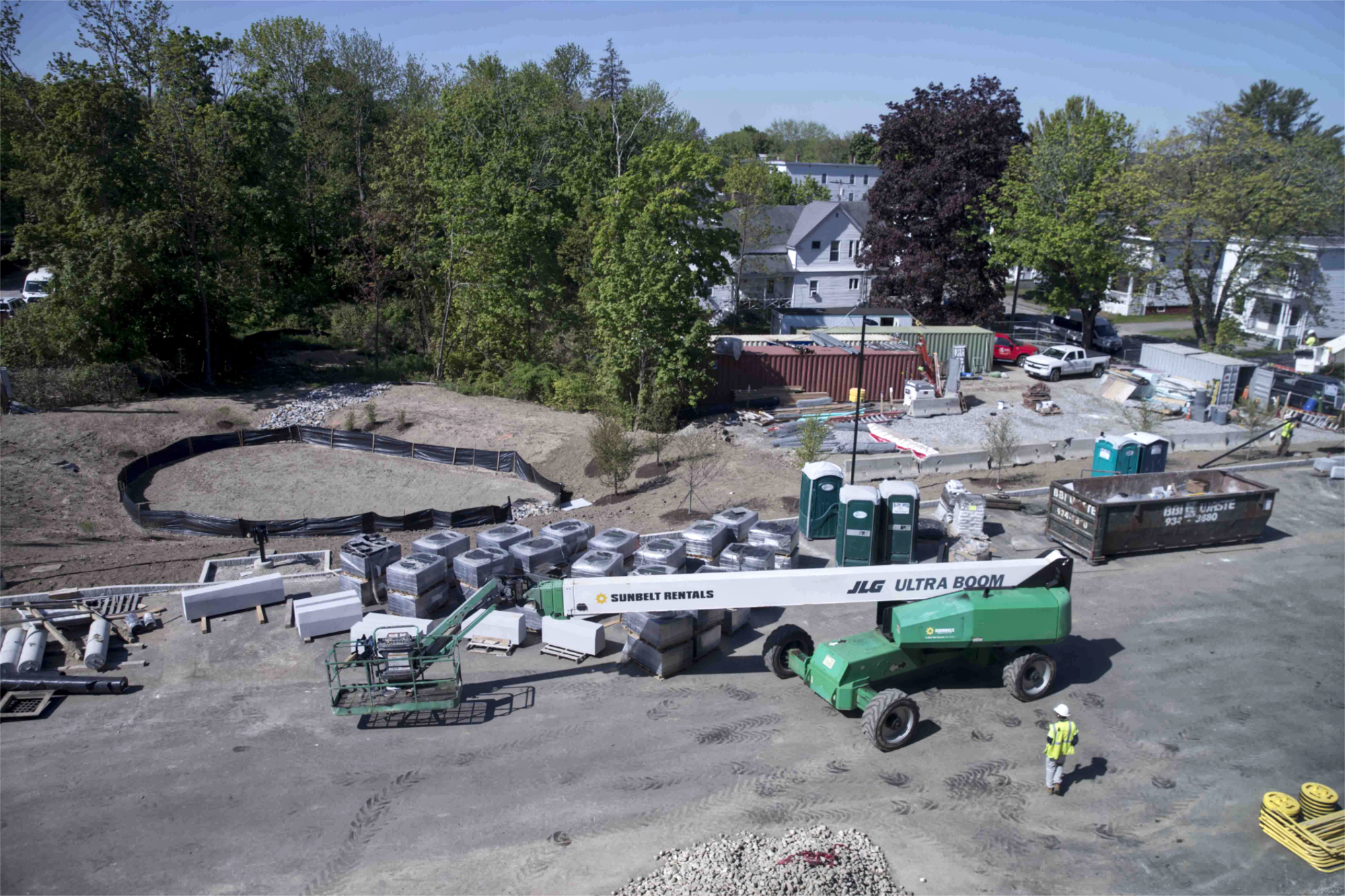 The south side of the Bonney Science Center lot is shown from the roof on May 17. Note the stormwater detention basin at left and the pallets of hardscaping materials. The leftmost of the Jersey barriers is near the former site of the Campus Construction Update penthouse. (Phyllis Graber Jensen/Bates College)