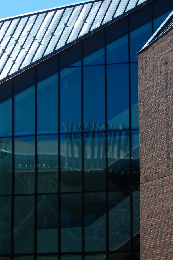 Carnegie Science Hall's rooftop exhaust stacks are reflected in the Bonney Center's Monumental Stair curtain wall. (Doug Hubley/Bates College)