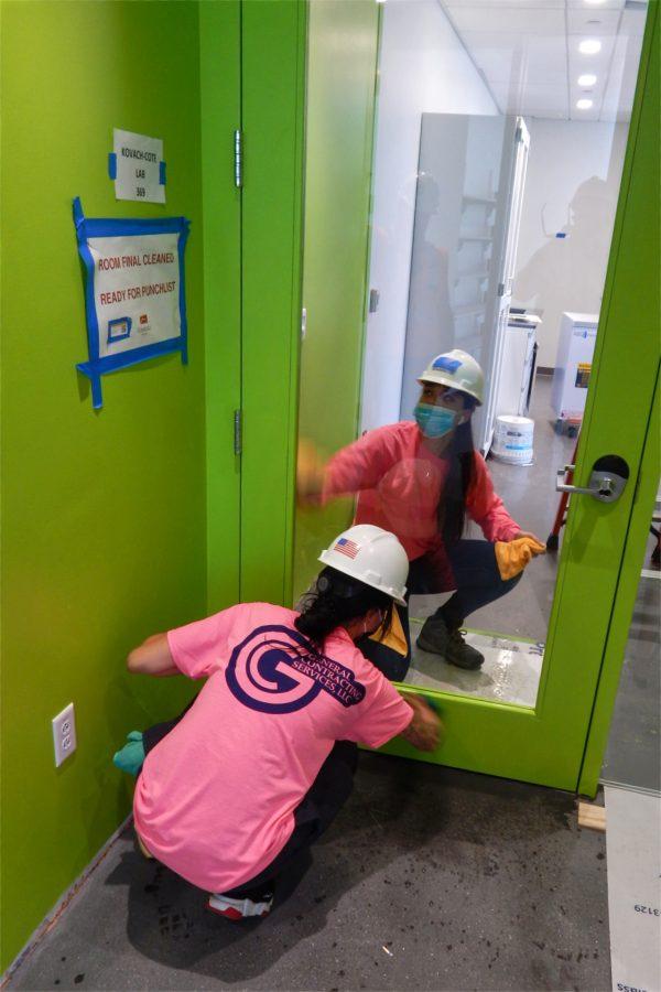 Employees of General Contracting Services of Woburn, Mass., clean a third-floor door. (Doug Hubley/Bates College)