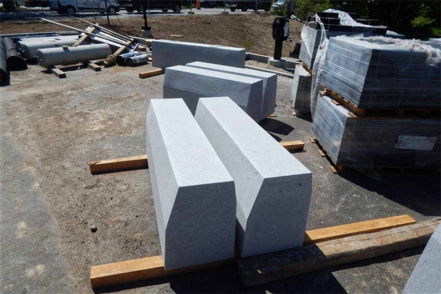 These concrete benches will be placed on the Bonney Science Center grounds. They resemble the benches found on Alumni Walk. At right are pallets of asphalt pavers; at rear is a charging station for electric vehicles. (Doug Hubley/Bates College)