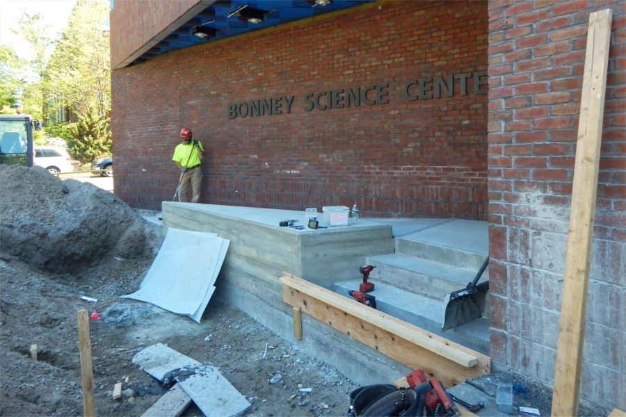 A Consigli Construction employee at work on steps at the Bonney building's Nichols Street entrance. (Doug Hubley/Bates College)