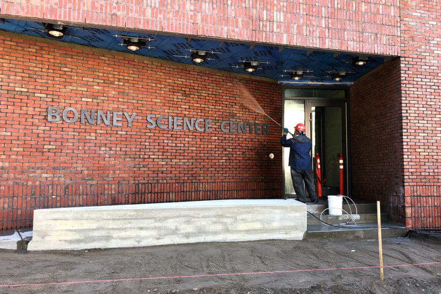 A worker power-washes brickwork at the Nichols Street entrance to the Bonney Science Center. (Jay Burns/Bates College)