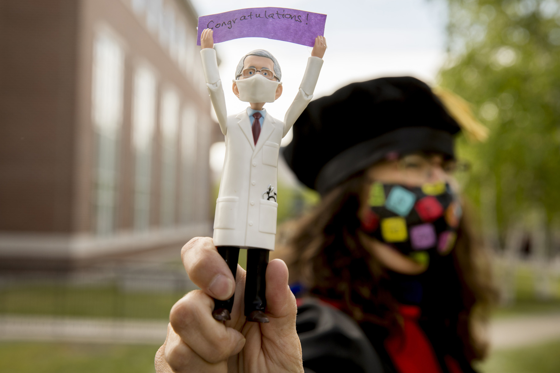 """Professor of Chemistry and Biochemistry Paula Schlax displays a Dr. Anthony Fauci action figure holding the word """"Congratulations"""" prior to the morning Commencement procession on May 27, 2021. Fauci received an honorary degree from Bates in 1993. (Phyllis Graber Jensen/Bates College)"""