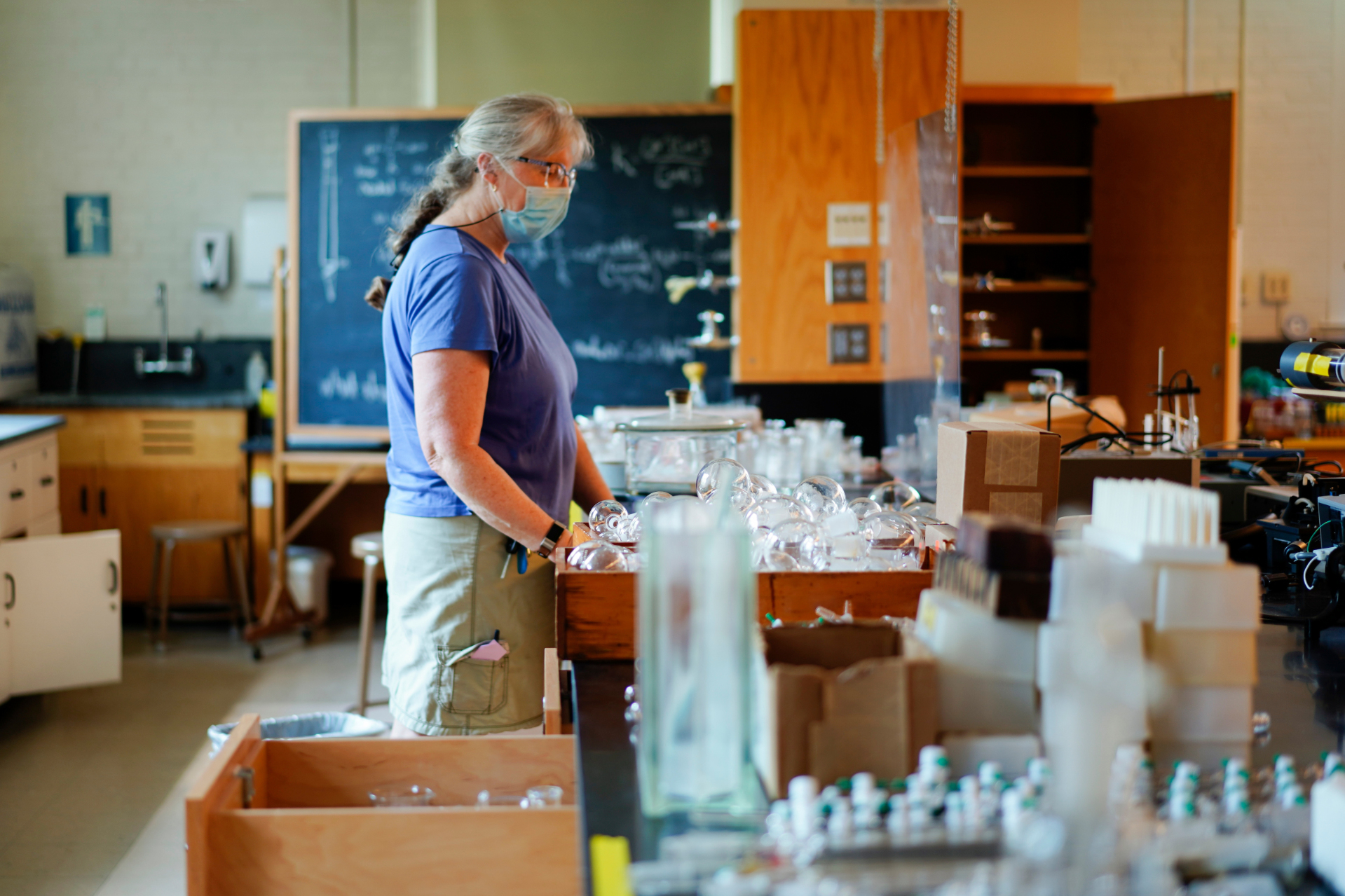 Lorna Clark, in her 30th year of employment with Bates as an assistant in instruction with the departments of chemistry and biochemistry, packs up glassware in the advanced chemistry laboratory on Dana Chemistry Hall's third floor. (Phyllis Graber Jensen/Bates College)