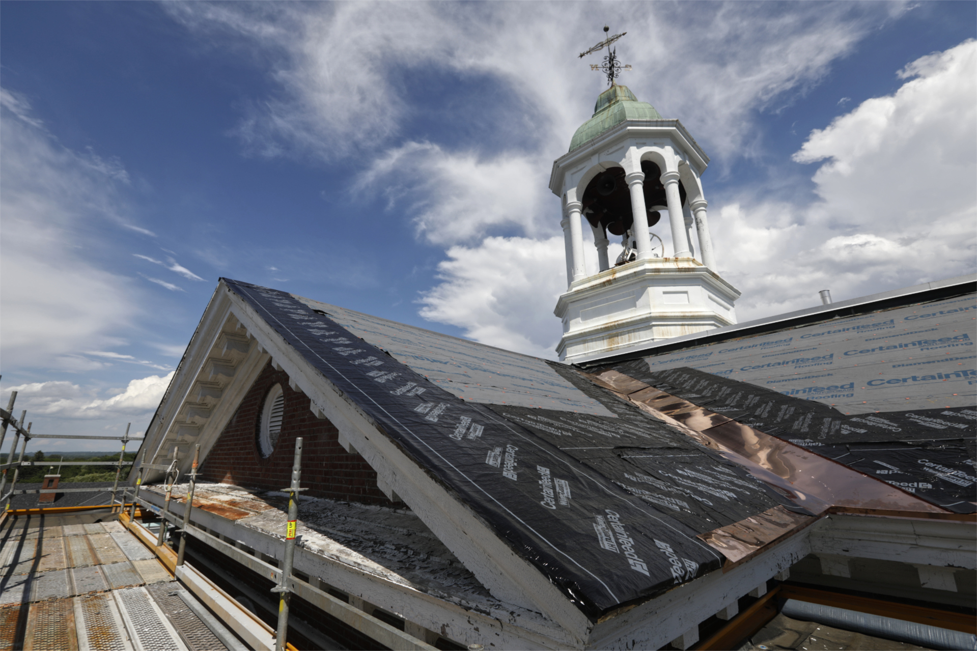 With the century-old slate removed from Hathorn's roof, new weather barrier and copper flashing have been placed in preparation for the new slate in this June 30 image. (Theophil Syslo/Bates College)