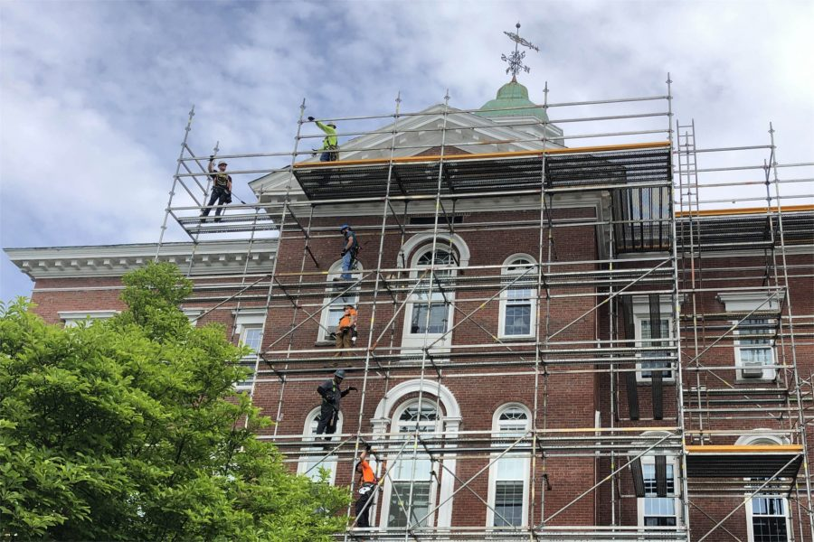 Workers for G&E Roofing are shown on on June 3 on  staging erected around Hathorn Hall in connection with the replacement of the building's roof. (Jay Burns/Bates College)